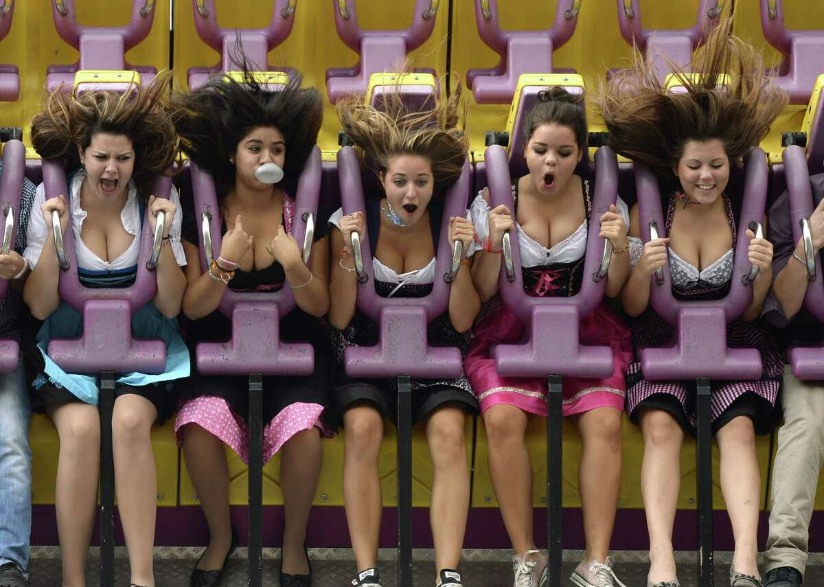 Young women in traditional Bavarian Dirndl dresses enjoy a fun ride during the Oktoberfest beer festival at the Theresienwiese fair grounds in Munich, southern Germany, on the fair's opening day on September 21, 2013. The world's biggest beer festival Oktoberfest will run until October 6, 2013.