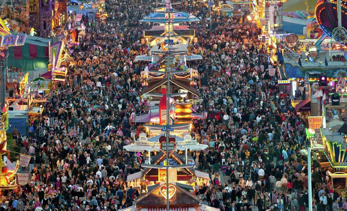 Visitors walk through a crowded street during sunset at the Oktoberfest 2013 beer festival at Theresienwiese on September 21, 2013 in Munich, Germany.