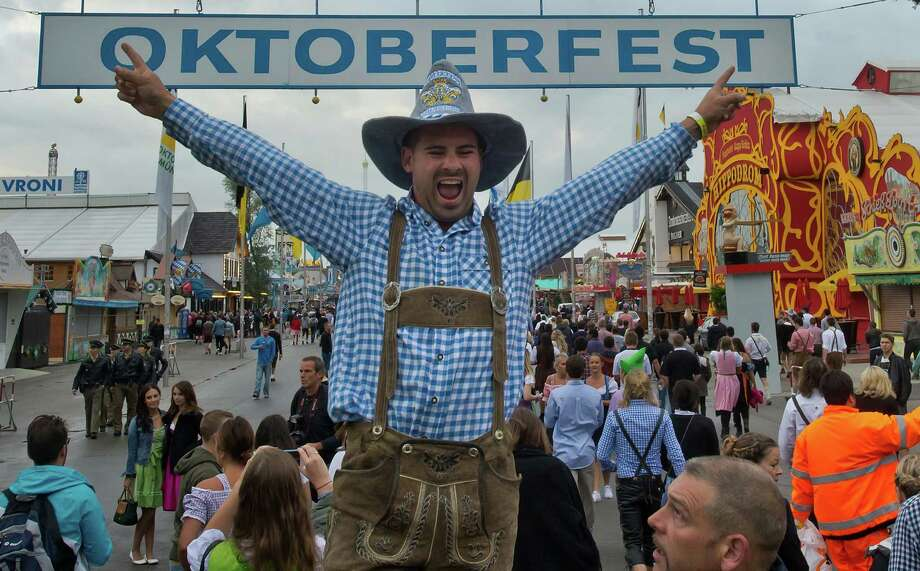 A Visitor in bavarian style clothes jubilates in front of the main entrance of the Oktoberfest 2013 beer festival at Theresienwiese on September 21, 2013 in Munich, Germany. M Photo: Joerg Koch, Getty Images / 2013 Getty Images