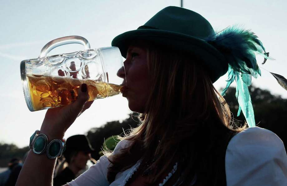 A woman drinks beer outside a beer tent during day 1 of the Oktoberfest 2013 beer festival at Theresienwiese on September 21, 2013 in Munich, Germany. Photo: Johannes Simon, Getty Images / 2013 Getty Images