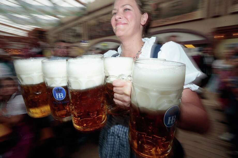A waitress carries beer mugs after tapping the first barrel during day 1 of the Oktoberfest 2013 beer festival at Theresienwiese on September 21, 2013 in Munich, Germany. Photo: Johannes Simon, Getty Images / 2013 Getty Images