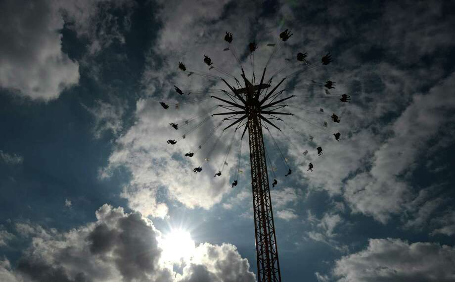 Visitors sit on a fun ride during the Oktoberfest beer festival at the Theresienwiese fair grounds in Munich, southern Germany, on the festival's opening day on September 21, 2013. The world's biggest beer festival Oktoberfest will run until October 6, 2013. Photo: CHRISTOF STACHE, AFP/Getty Images / AFP