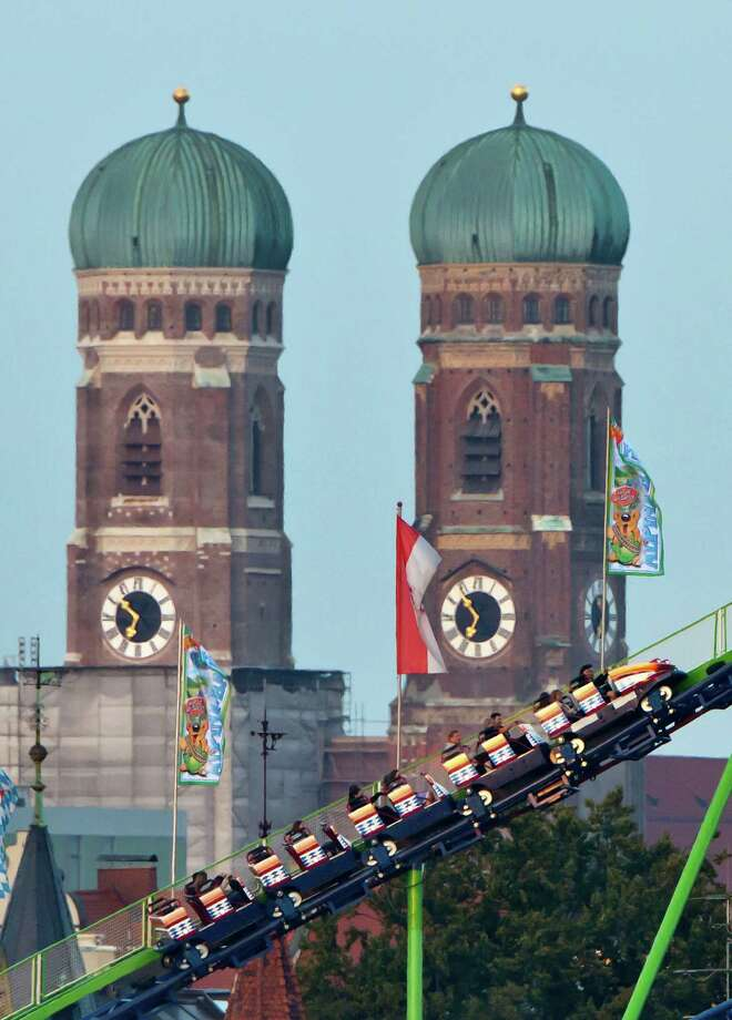 Visitors enjoy amusement rides in front of the famous backdrop of Munich Frauenkirche at the Oktoberfest 2013 beer festival at Theresienwiese on September 21, 2013 in Munich, Germany. The Munich Oktoberfest, which this year will run from September 21 through October 6, is the world's largest beer fest and draws millions of visitors. Photo: Joerg Koch, Getty Images / 2013 Getty Images