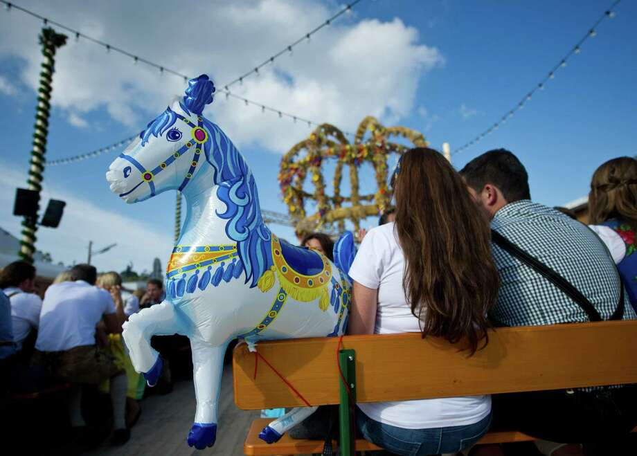 A man and a woman with a horse-designed balloon sit on a bench during the Oktoberfest beer festival on the Theresienwiese fair grounds in Munich, southern Germany, on September 21, 2013. The world's biggest beer festival Oktoberfest will run until October 6, 2013. Photo: INGA KJER, AFP/Getty Images / DPA