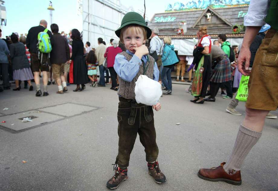 A boy in traditional Bavarian Lederhosen (leather trousers) eats a candy floss at the Oktoberfest beer festival on the Theresienwiese fair grounds in Munich, southern Germany, on September 21, 2013. The world's biggest beer festival Oktoberfest will run until October 6, 2013. Photo: KARL-JOSEF HILDENBRAND, AFP/Getty Images / DPA