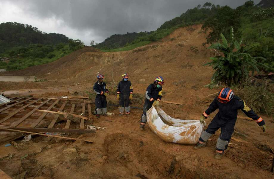Soldiers remove the body of a woman who was recovered from the site of a landslide in La Pintada. The village was the scene of the single greatest tragedy in destruction wreaked by Manuel and Ingrid, which pounded both of Mexico's coasts. Photo: Eduardo Verdugo / Associated Press