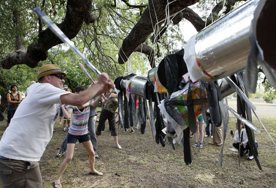 Justis Langford hits a piñata that represents the Keystone XL pipeline during a protest at San Pedro Springs Park organized by 350.org. Langford said he thinks the real cost of the pipeline would outstrip its short-term benefits. Photo: For The San Antonio Express-News