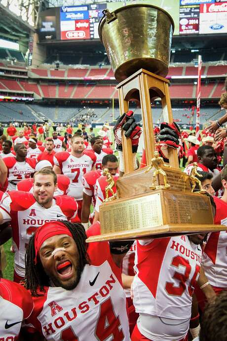 Houston defensive backs Jarrett Irving (14) and Steven Aikens (39) carry the Bayou Bucket off the Reliant Stadium field after beating Rice and claiming the trophy for the third consecutive year. Photo: Smiley N. Pool, Staff / © 2013  Houston Chronicle