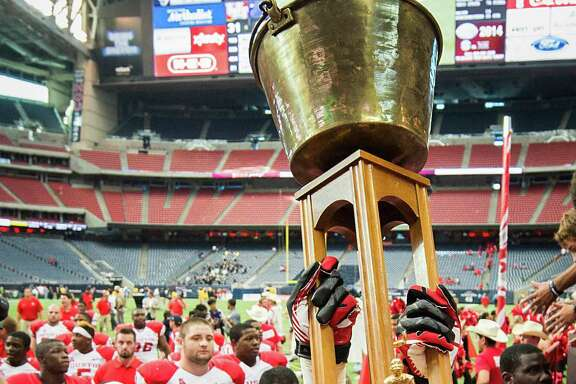 Houston defensive backs Jarrett Irving (14) and Steven Aikens (39) carry the Bayou Bucket off the Reliant Stadium field after beating Rice and claiming the trophy for the third consecutive year.