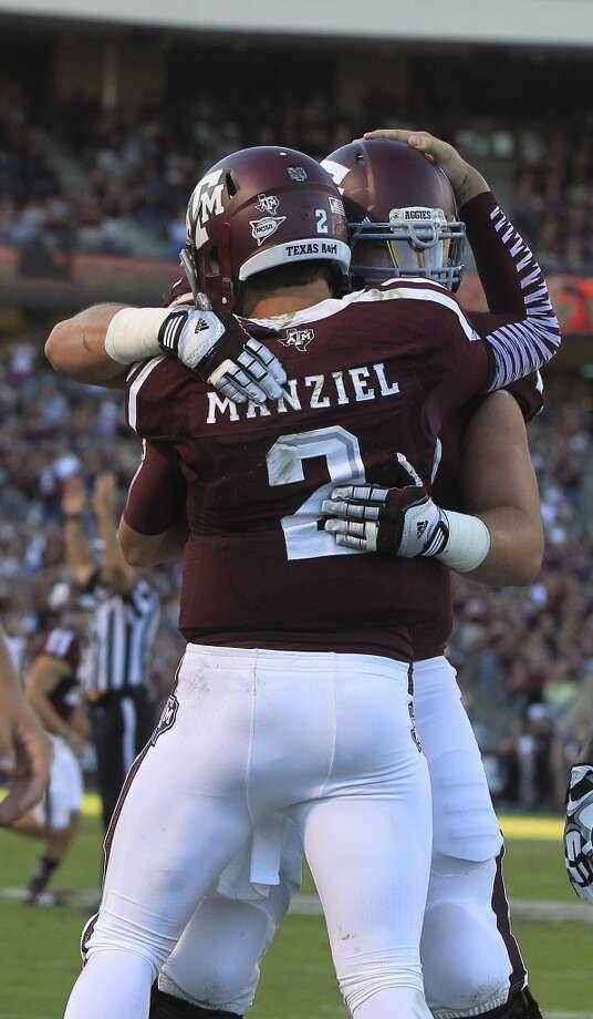 Texas A&M Aggies quarterback Johnny Manziel (2) celebrates his touchdown with teammates during the first quarter. Photo: Karen Warren, Houston Chronicle