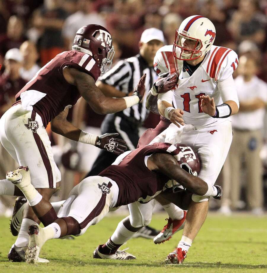 Southern Methodist Mustangs quarterback Garrett Gilbert (11) gets brought down by Texas A&M Aggies defensive back Toney Hurd Jr. (4) during the third quarter. Photo: Karen Warren, Houston Chronicle