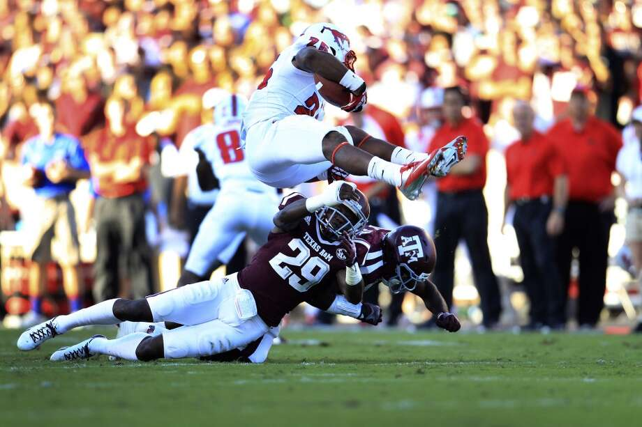 Texas A&M Aggies defensive back Deshazor Everett (29) upends Southern Methodist Mustangs running back K.C. Nlemchi (25) during the first quarter of a college football game at Kyle Stadium, Saturday, Sept. 21, 2013, in Houston. ( Karen Warren / Houston Chronicle ) Photo: Houston Chronicle