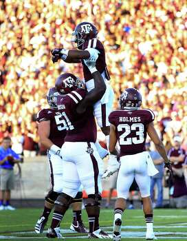 A&M running back Ben Malena gets a big lift from lineman Jarvis Harrison after scoring on a 3-yard run in the first quarter. Photo: Karen Warren, Staff / © 2013 Houston Chronicle