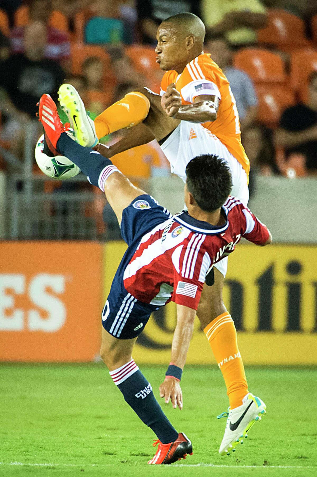 Dynamo midfielder Ricardo Clark fights for the ball against Chivas USA midfielder Carlos Alvarez.