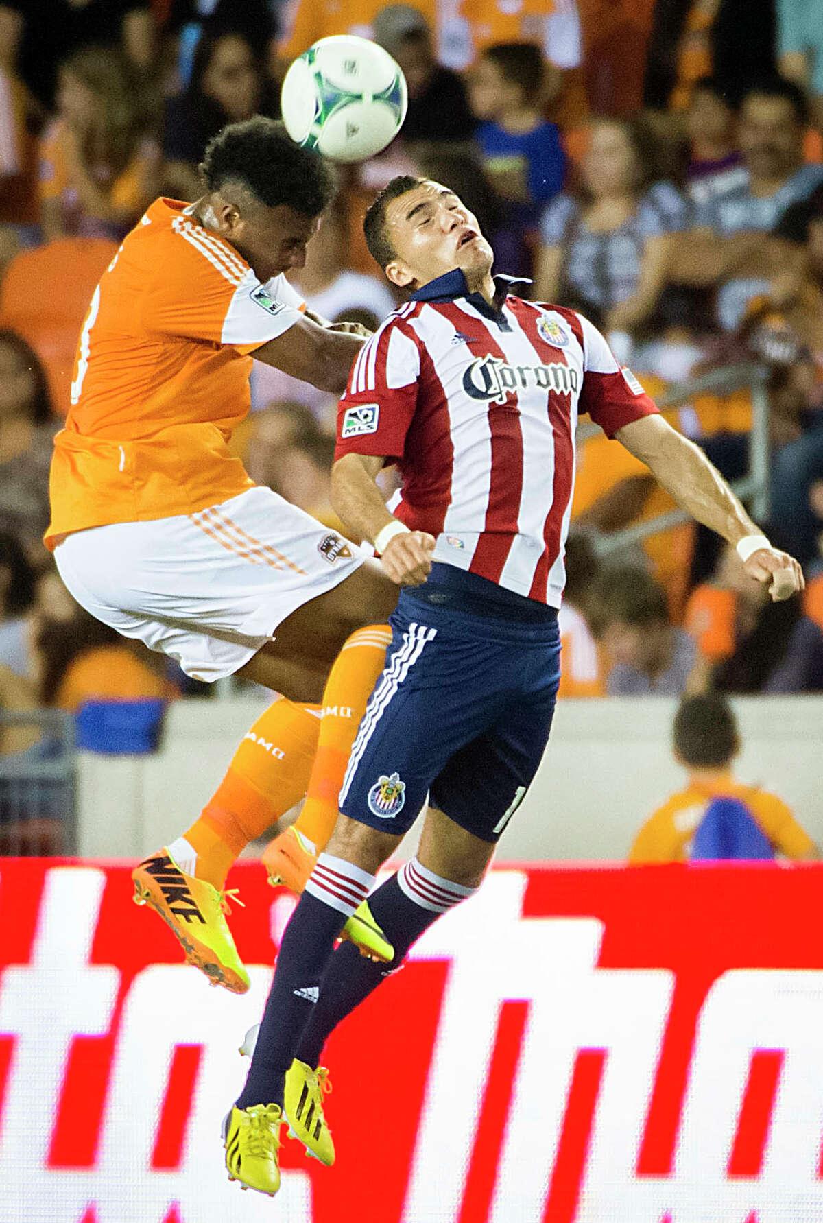 Dynamo midfielder Giles Barnes fights for a header against Chivas USA defender Bryan de la Fuente.