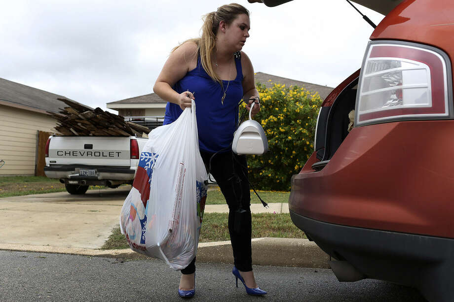 FORCED OUT: Krystle Perry packs her car with her belongings from her former house on the East Side. The home was purchased by DTND Sierra Investments LLC at a foreclosure auction. Photo: Lisa Krantz / San Antonio Express-News