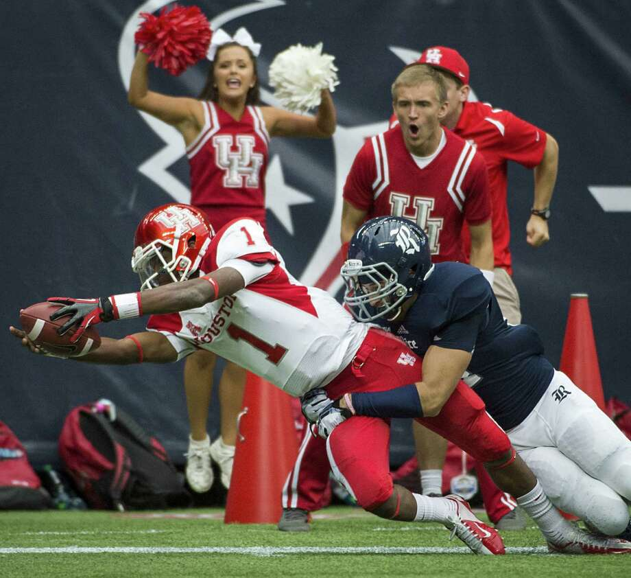 Greg Ward, one of two quarterbacks Houston used Saturday, just misses a score as Rice safety Paul Porras brings him down in the first half. Photo: Smiley N. Pool / Houston Chronicle