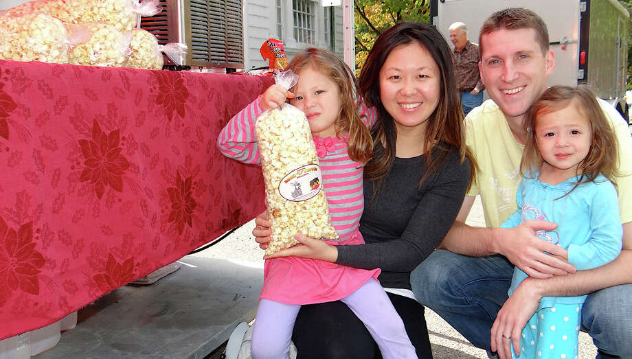 The Witinok family -- Emma, 4; Ellen, Dan and Alice, 2 -- enjoyed a big bag of kettle corn Saturday at the Fairfield Kiwanis Club's Arts & Crafts Fair on Town Hall Green. Photo: Mike Lauterborn / Fairfield Citizen contributed