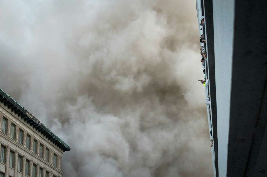 A large cloud of dust heads for spectators watching from a parking garage during the implosion of the landmark former Macy's department store building in downtown Houston on Sunday, Sept. 22, 2013. Photo: Smiley N. Pool, Houston Chronicle / © 2013  Houston Chronicle