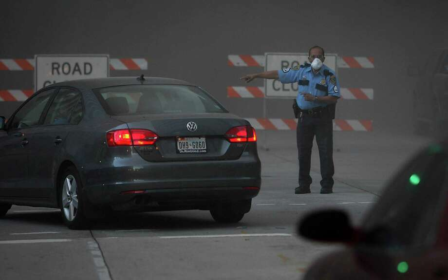 A Houston Police officer directs traffic in the debris dust cloud during the implosion of the Macy's building downtown on Sunday, Sept. 22, 2013. Photo: James Nielsen, Houston Chronicle / © 2013  Houston Chronicle