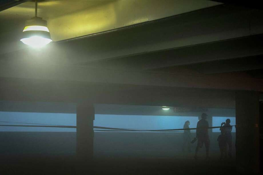 Spectators head for their cars in a parking garage as a large cloud of dust rolls through downtown after the implosion of the former Macy's department store building in downtown Houston on Sunday, Sept. 22, 2013. Photo: Smiley N. Pool, Houston Chronicle / © 2013  Houston Chronicle