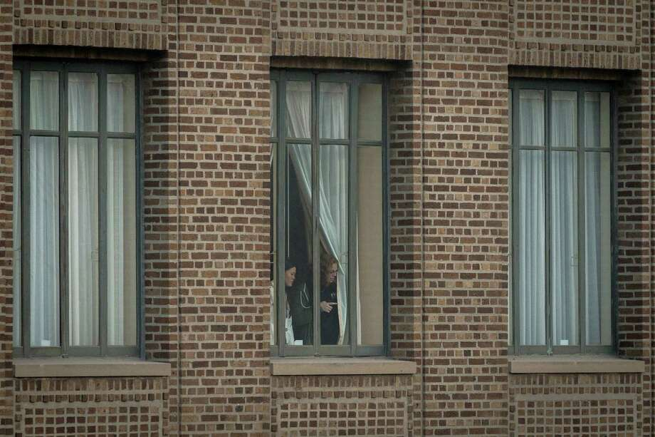 People peek from windows of a Residence Inn after the implosion of the former Macy's department store building in downtown Houston on Sunday, Sept. 22, 2013. Photo: Smiley N. Pool, Houston Chronicle / © 2013  Houston Chronicle