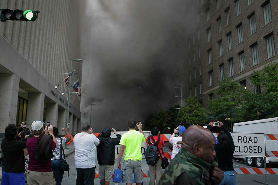 Spectators photograph the debris dust cloud during the implosion of the Macy's building in downtown Houston on Sunday, Sept. 22, 2013. Photo: James Nielsen, Houston Chronicle / © 2013  Houston Chronicle