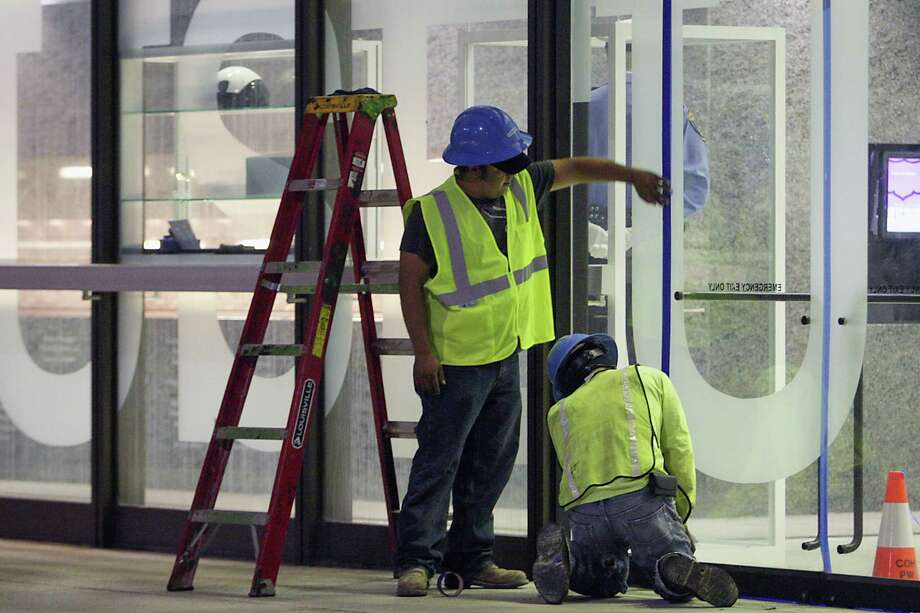 Workers tape the door seams on a building prior to the implosion of the Macy's building in downtown Houston on Sunday, Sept. 22, 2013. Photo: James Nielsen, Houston Chronicle / © 2013  Houston Chronicle