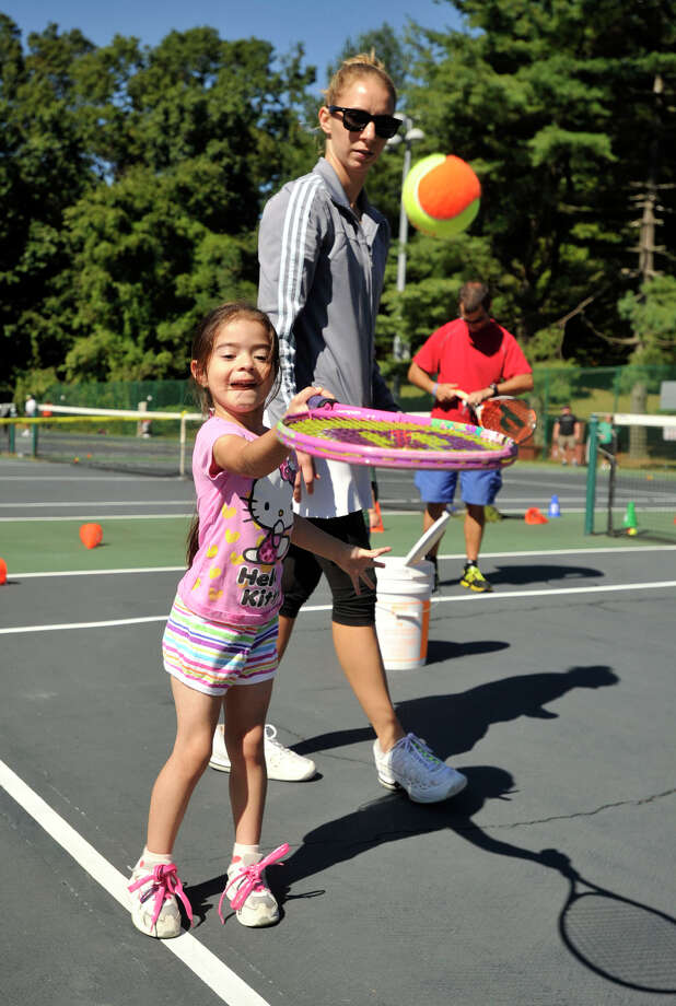 Instructor Jackie Visinski watches over Samantha Flores as she works on her swing during the USTA Free Tennis Play Event at Scalzi Park in Stamford on Sunday, Sept. 22, 2013. Photo: Jason Rearick / Stamford Advocate