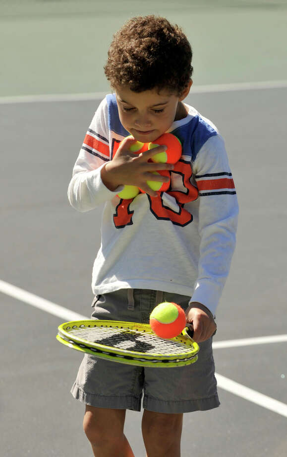 Milan Labriola shags tennis balls during the USTA Free Tennis Play Event at Scalzi Park in Stamford on Sunday, Sept. 22, 2013. Photo: Jason Rearick / Stamford Advocate
