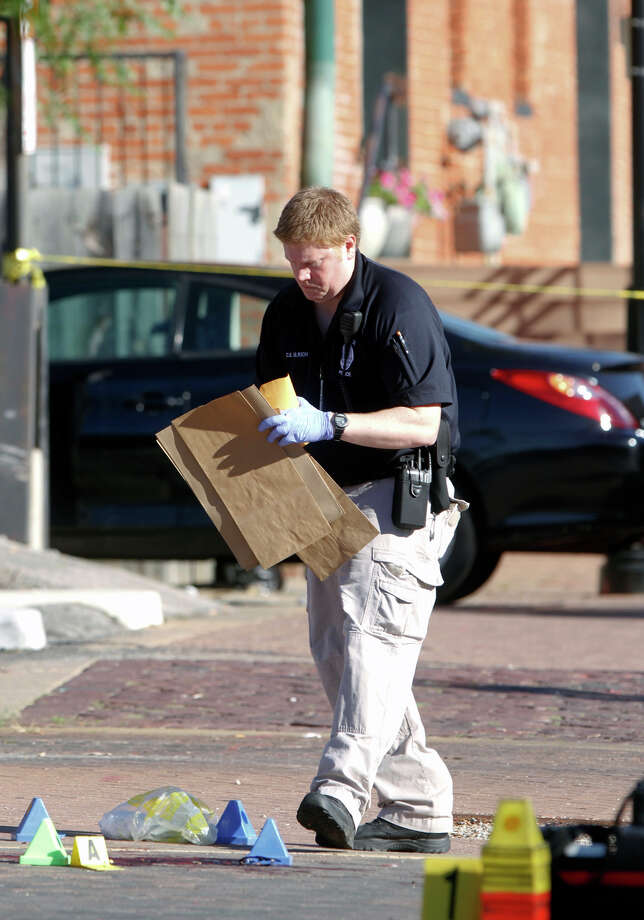 A Wichita Crime Scene Investigator picks up evidence at the scene of a shooting in the Old Town neighborhood of Wichita, Kan. on Sunday, Sept. 22, 2013. Officials say at least one man has died and five have been injured in the shooting. Photo: AP