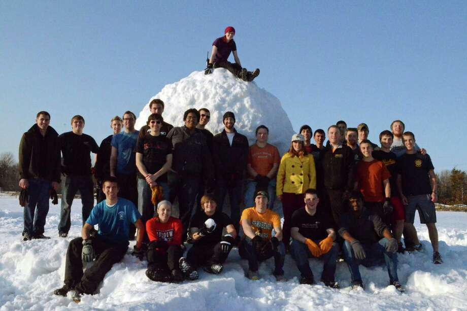In this March 29, 2013, photo provided by the Michigan Technological University, students at Michigan Technological University pose for a photo with a giant snowball they rolled in Houghton, Mich. The school recently received notice that the snowball, which has a circumference of 32.94 feet and weighed several tons, was certified as the world's largest snowball by Guinness World Records. Photo: AP