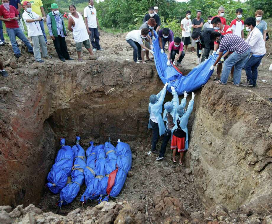 Volunteers bury the bodies of Muslim rebels killed in the 12-day standoff in a common grave at the outskirts of Zamboanga city in southern Philippines Friday Sept. 20, 2013. The ongoing standoff between government forces and Muslim rebels, who seized several hostages and used them as human shields, has now displaced more than 100,000 people and resulted in billions of pesos (millions of dollars) losses to the city's business and resulted in the death of at least 60 people. Photo: AP