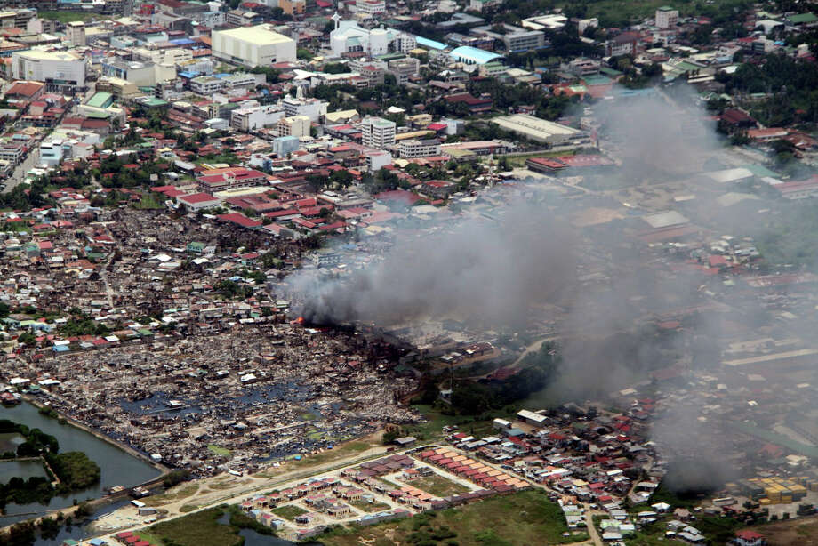 In this Tuesday, Sept. 17, 2013 photo released by the Philippine Air Force, a fire breaks out at a village in Zamboanga city where government troops battle a holdout group of Muslim rebels holding hostages in southern Philippines. It was the most serious fighting in years between rebels and government forces in the predominantly Roman Catholic nation's south, the scene of decades-old struggle for self-rule by minority Muslims. (AP Photo/Philippine Air Force) NO SALES Photo: AP
