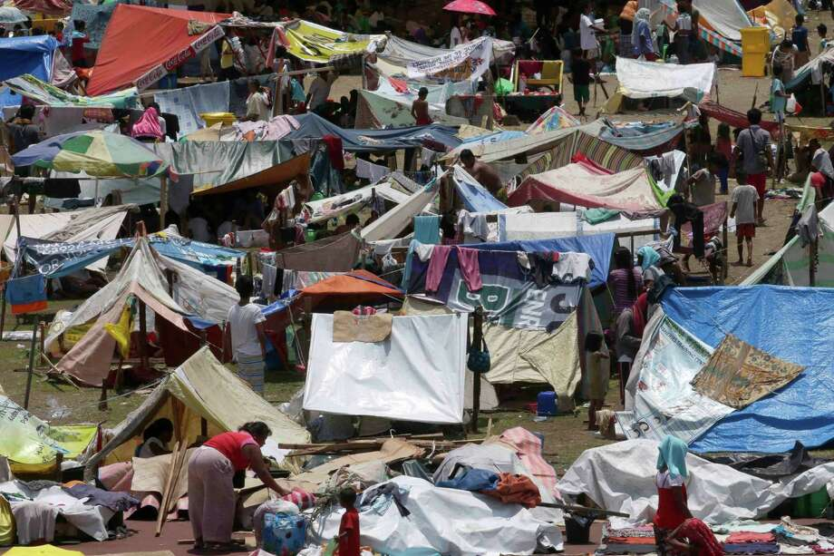 Villagers, who were displaced by the fighting between government forces and Muslim rebels in Zamboanga city in southern Philippines, continue to be housed in tents on a stadium Friday Sept. 20, 2013. The ongoing standoff  has now displaced more than 100,000 people and resulted in billions of pesos (millions of dollars) losses to the city's business. Photo: AP