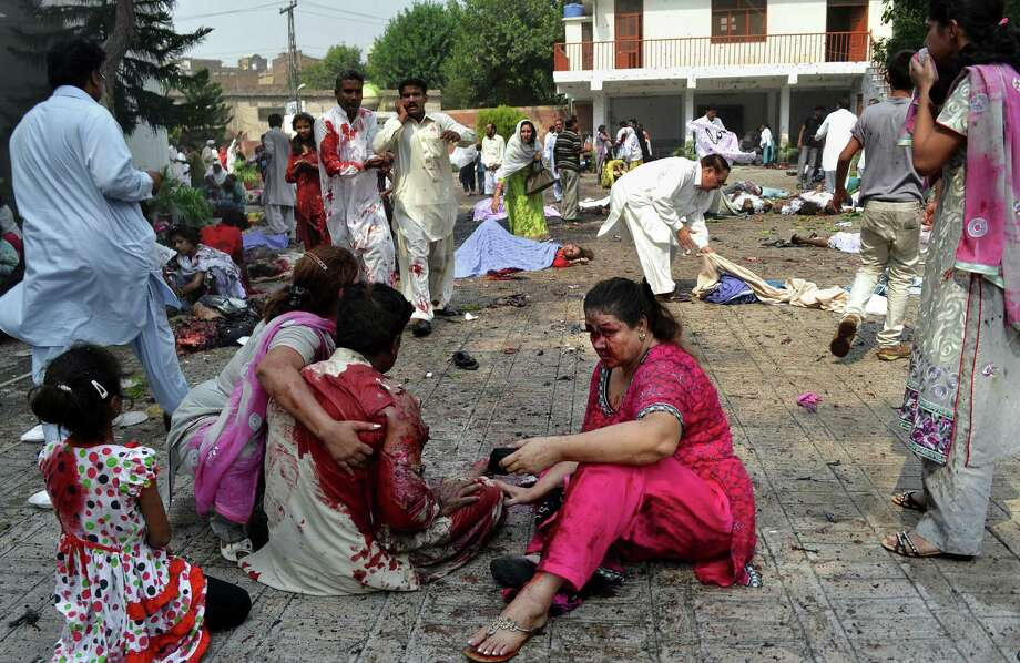 Pakistanis help victims of a suicide attack at a church in Peshawar, Pakistan, Sunday, Sept. 22, 2013. A suicide bomb attack on the historic church killed scores of people on Sunday, officials said, in one of the worst assaults on the country's Christian minority in years. Photo: AP