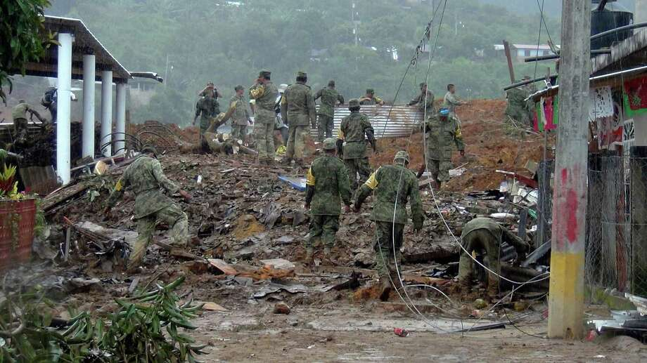 Soldiers search through mud and rubble for bodies, victims of a landslide in the town of La Pintada, Mexico, Saturday, Sept. 21, 2013. Dozens remained missing in La Pintada, where soldiers continued digging after a landslide caused by the one-two punch of storms Manuel and Ingrid, wiped out half of the town. Photo: AP