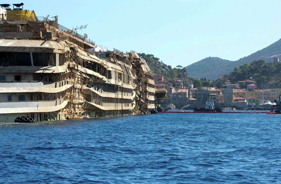 "The once underwater side of the Costa Concordia is visible after it was lifted upright, on the Tuscan Island of Giglio, Italy, Wednesday, Sept. 18, 2013. The crippled cruise ship was pulled completely upright early Tuesday after a complicated, 19-hour operation to wrench it from its side where it capsized last year off Tuscany, with officials declaring it a ""perfect"" end to a daring and unprecedented engineering feat. Photo: AP"