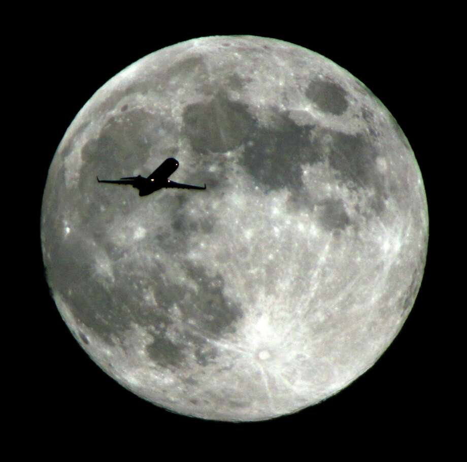 An airlines jet plane approaching Los Angeles International Airport crosses the moon as seen from Monterey Park Calif., Wednesday night ,  Sept 18,  2013. The Harvest Moon is the full moon that falls closest to the autumnal equinox (this year it falls on this coming Sunday), which marks the beginning of fall in the Northern Hemisphere. Photo: AP