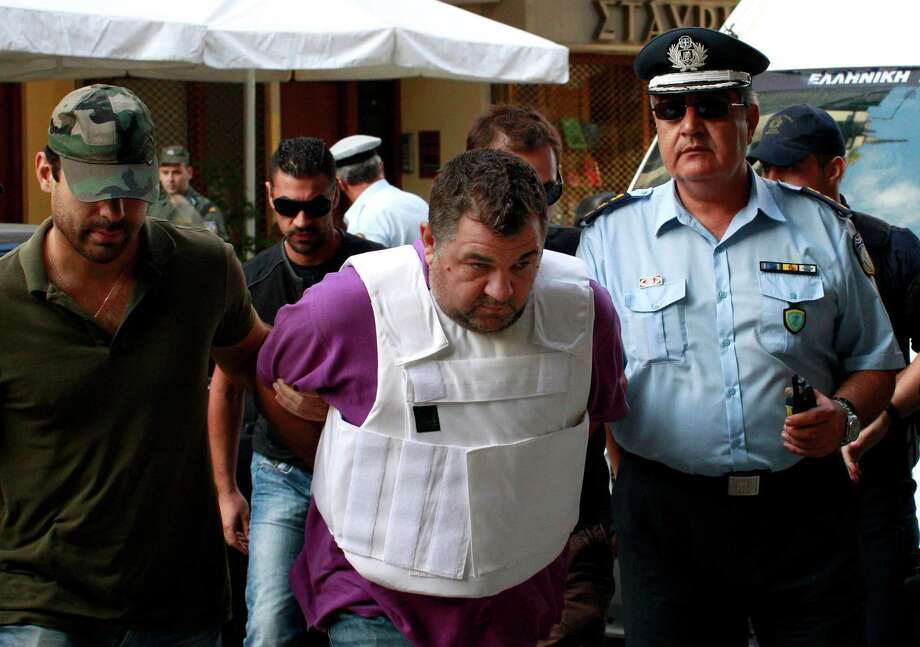 Policemen escort a man, center, accused in the fatal stabbing of a 34-year-old musician described as an anti-fascist activist, as they arrive at the prosecutor's office in Piraeus, near Athens, Greece, Saturday, Sept. 21, 2013. Greece's anti-terrorism division has taken over the investigation into the murder of anti-fascist rapper Pavlos Fyssas, blamed on a supporter of the far-right Golden Dawn Party, the Public Order Ministry said Friday. The order followed the arrest of the 45-year-old suspect in the fatal stabbing early Wednesday. In the wake of the slaying, the government also appealed to a Supreme Court prosecutor to investigate more than 30 offenses it says are linked to the ultranationalist party. Photo: AP