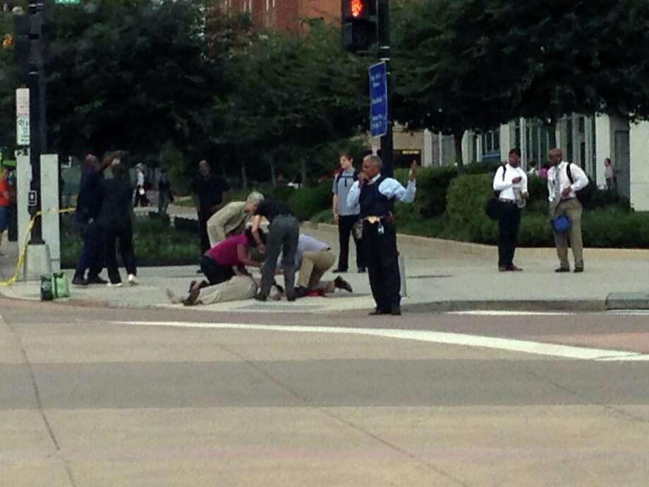 In this photo, which The AP obtained from Don Andres, shooting victim Vishnu Pandit is assisted on the sidewalk while awaiting the arrival of emergency medical personnel after coworkers took him by car from the Washington Navy Yard to receive medical attention Monday, Sept. 16, 2013, in Washington. Pandit died of his injuries. Photo: AP