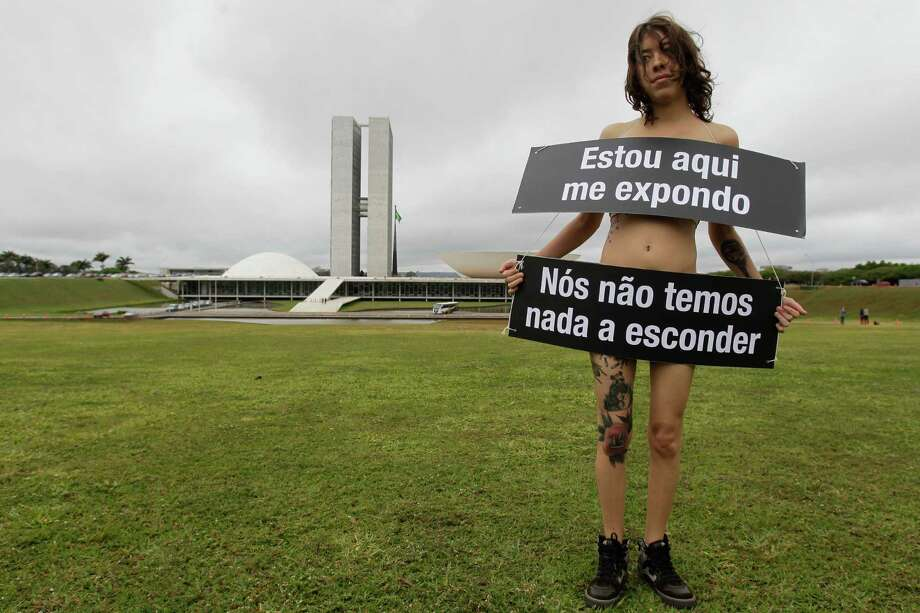 "A demonstrator from the Avaaz organization wears signs that read in Portuguese ""I'm here exposing myself. We have nothing to hide"" outside Congress to protest secret voting in Brasilia, Brazil, Wednesday, Sept. 18, 2013. Demonstrators are asking for congressional voting be opened to the public. Photo: AP"