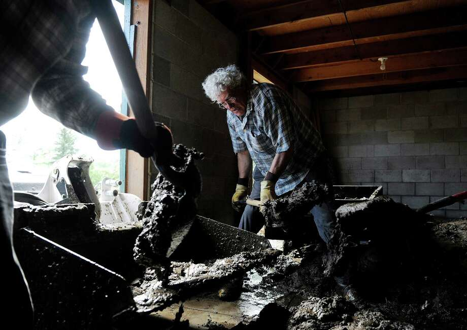 Stan Koleski, 65, shovels mud from a friend's barn in Loveland, Colo., on Wednesday, Sept. 18, 2013. The Big Thompson River went over its banks destroying homes and businesses in the area. Statewide, only about 22,000 homeowners have flood insurance policies, FEMA spokesman Jerry DeFelice said. With 2.2 million housing units in Colorado, according to Census figures, that means about 1 percent of the state's residences have flood coverage. Photo: AP
