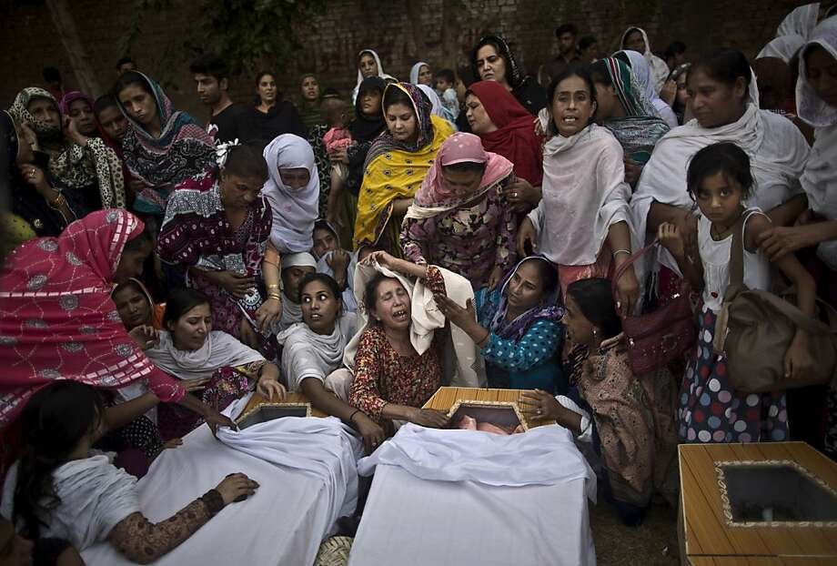 Female mourners, far left, grieve over the coffins of relatives who were killed in a suicide bombing at All Saints Church in Peshawar, Pakistan. Medical staff attend to a young victim, left. Photo: Muhammed Muheisen, Associated Press