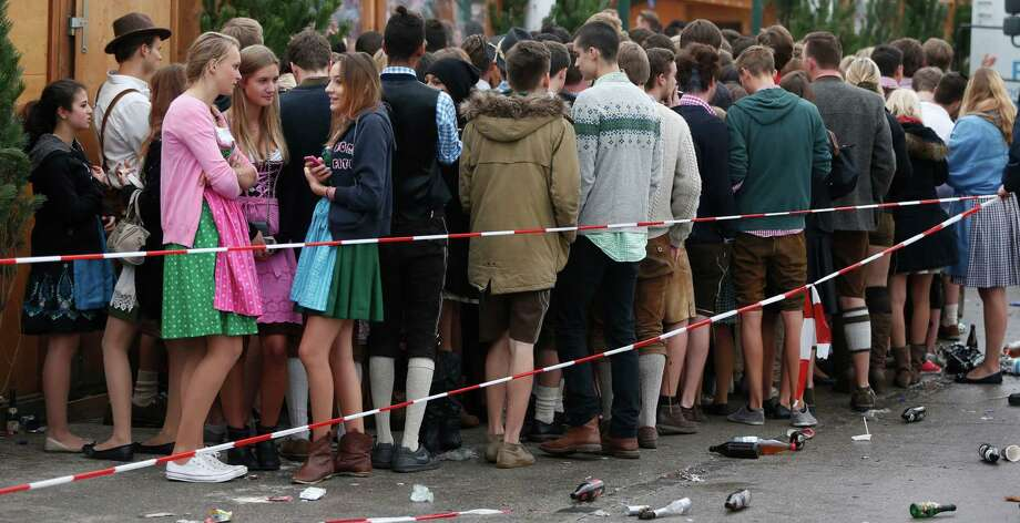 """People await the opening of the 180th Bavarian """"Oktoberfest"""" beer festival in Munich, southern Germany, Saturday, Sept. 21, 2013. The world's largest beer festival, to be held from Sept. 21 to Oct. 6, 2013, is expected to attract more than six million guests from around the world. Photo: AP"""