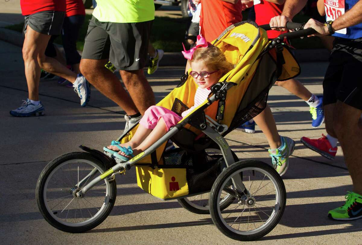A youngster gets a ride during the 3rd Annual Running of the Bulls 5K Run/Walk at Reliant Park on Sunday, Sept. 22, 2013, in Houston. Over 5,500 people participated in the event with the proceeds benefiting the Houston Texans Foundation and Houston Methodist.