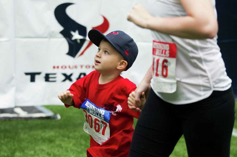 Jack Clark, 3, crosses the finish line with his mother Rebecca during the 3rd Annual Running of the Bulls 5K Run/Walk at Reliant Park on Sunday, Sept. 22, 2013, in Houston. Over 5,500 people participated in the event with the proceeds benefiting the Houston Texans Foundation and Houston Methodist. Photo: J. Patric Schneider, For The Chronicle / © 2013 Houston Chronicle