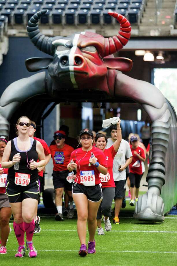 Runners crosse the finish line during the 3rd Annual Running of the Bulls 5K Run/Walk at Reliant Park on Sunday, Sept. 22, 2013, in Houston. Over 5,500 people participated in the event with the proceeds benefiting the Houston Texans Foundation and Houston Methodist. Photo: J. Patric Schneider, For The Chronicle / © 2013 Houston Chronicle