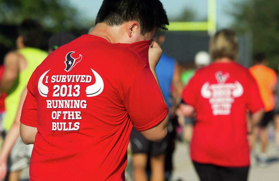 A runner dries his face as he runs the course during the 3rd Annual Running of the Bulls 5K Run/Walk at Reliant Park on Sunday, Sept. 22, 2013, in Houston. Over 5,500 people participated in the event with the proceeds benefiting the Houston Texans Foundation and Houston Methodist. Photo: J. Patric Schneider, For The Chronicle / © 2013 Houston Chronicle