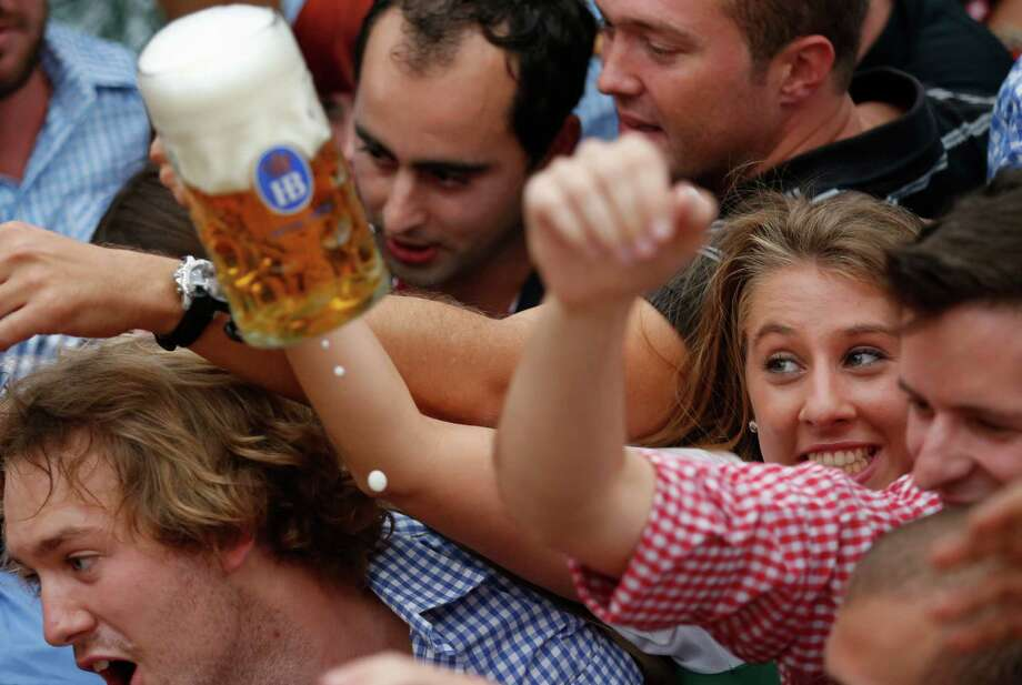 "Young people fight for beer during the opening ceremony in the ""Hofbraeuzelt' beer tent of the 180th Bavarian ""Oktoberfest"" beer festival in Munich, southern Germany, Saturday, Sept. 21, 2013. The world's largest beer festival, to be held from Sept. 21 to Oct. 6, 2013 will attract more than six million guests from around the world. Photo: AP"